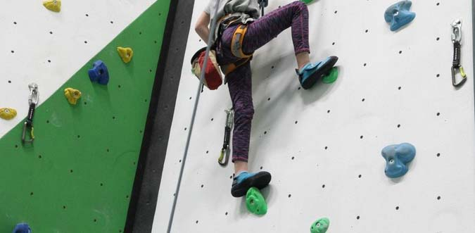 back of girl on climbing wall