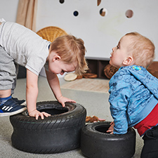 two boys playing onsmall tyres at nursery