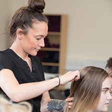 Hairdressing student brushing a clients hair