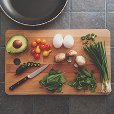Chopping board with vegetables and sharp knife