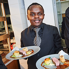 Hospitality student serving plates of food